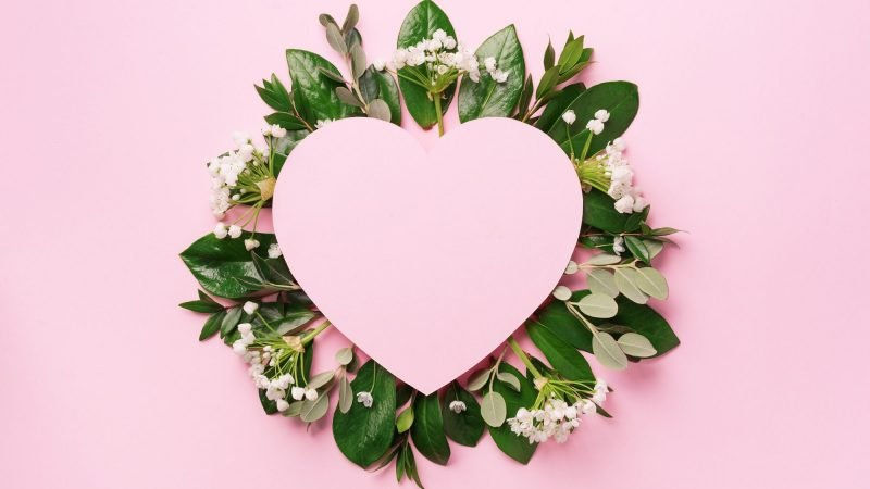 Tropical nature background with green leaves, white flowers and pink heart shaped paper for copy