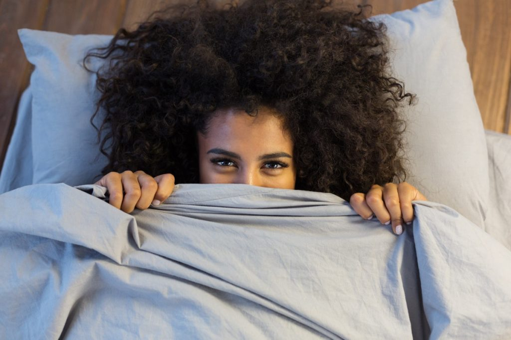 Beautiful african american woman smiling from behind her sheets and blankets