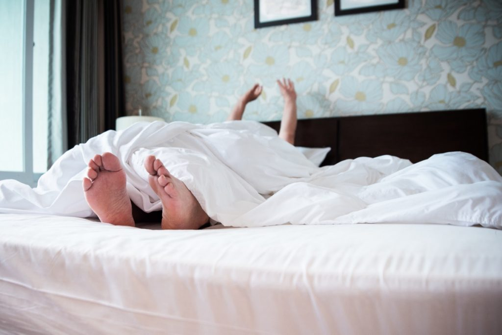 Sleepy woman in a very soft, luxurious bed