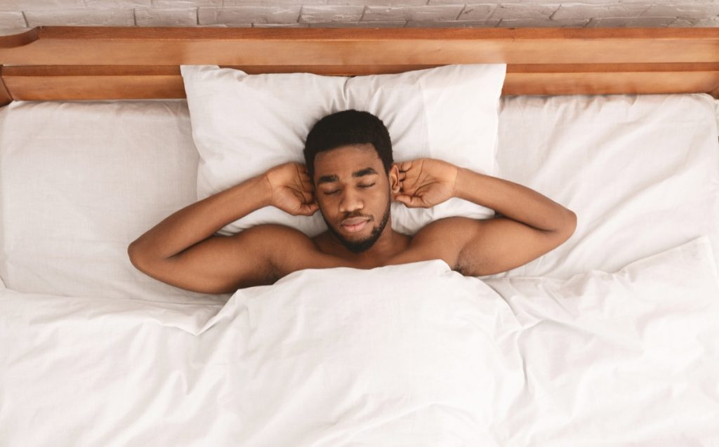 Relaxed african american man taking a nap relaxing in bed.