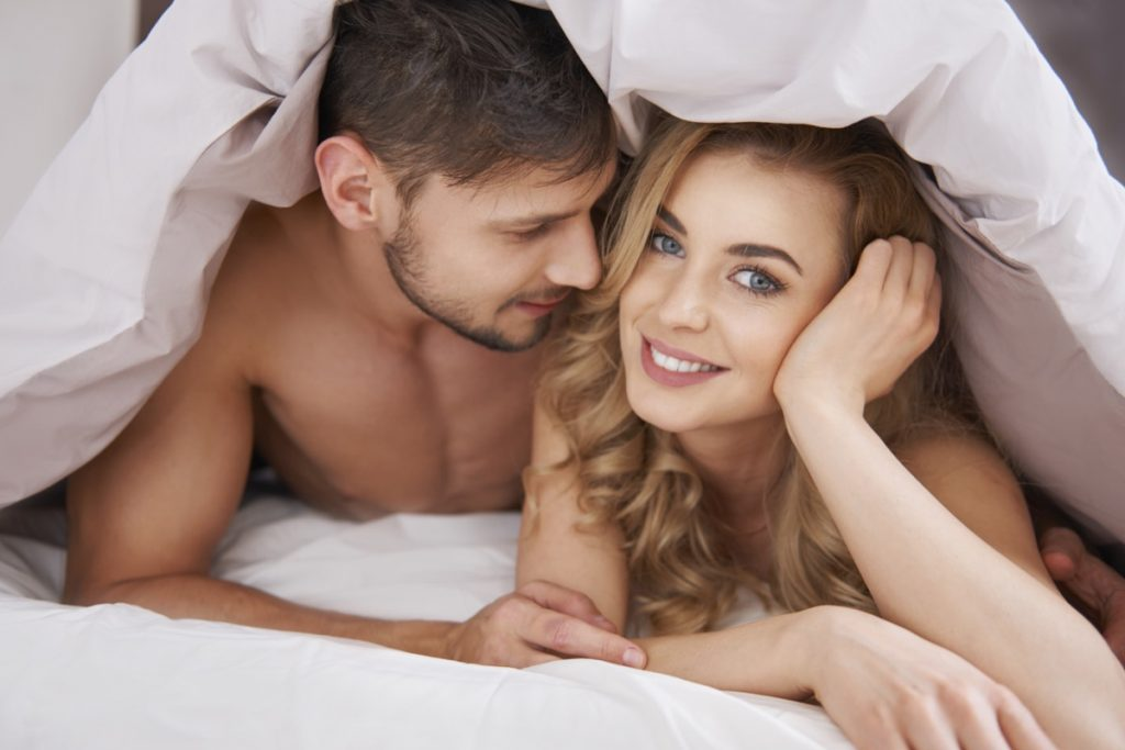 Fluffy white duvet bedspread and happy couple smiling at each other