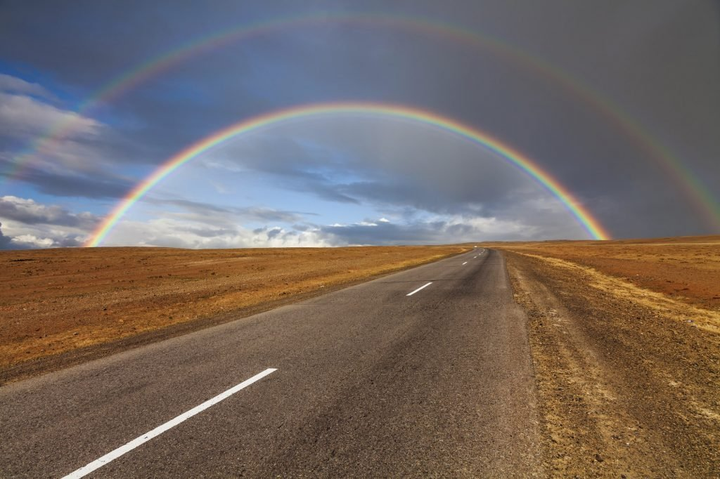 Lonely road in the desert under a rainbow
