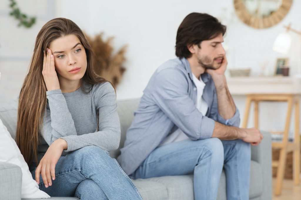 Upset young couple sitting on sofa at home, having conflict