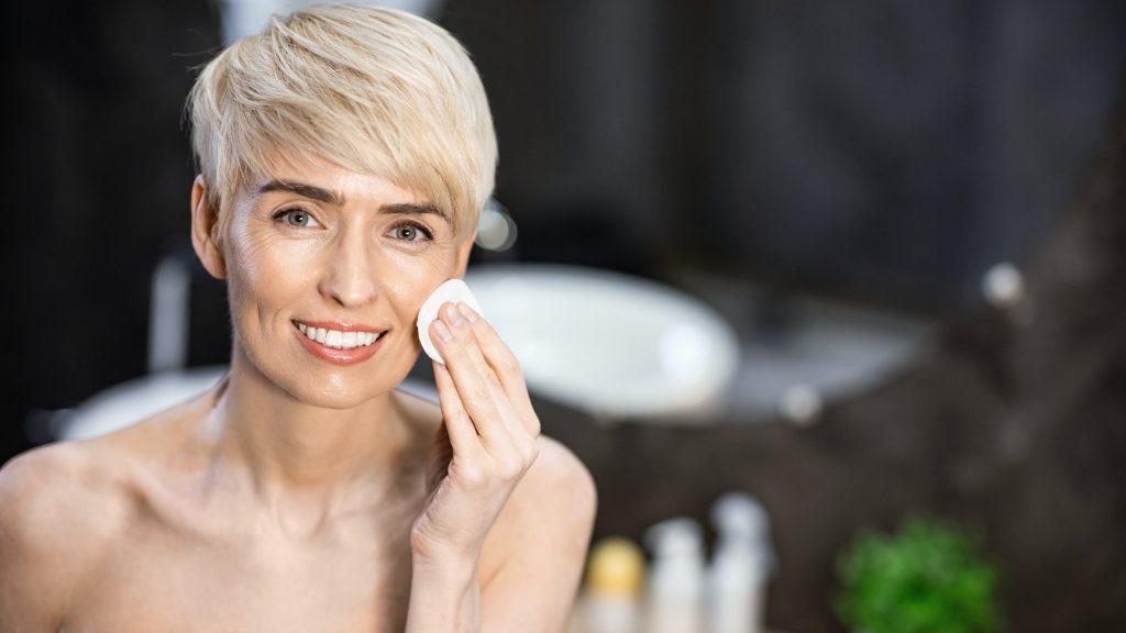 Woman Using Cotton Pad Moisturizing Skin Standing In Bathroom, Panorama